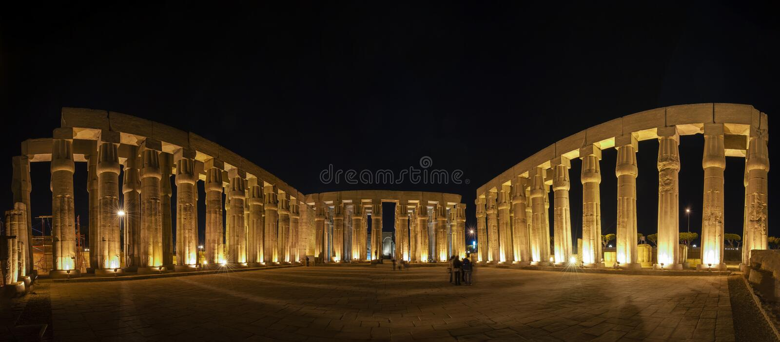 Panorama of large courtyard with ancient egyptian temple columns at night. Panoramic view of courtyard with large columns at the ancient egyptian Luxor temple royalty free stock photos