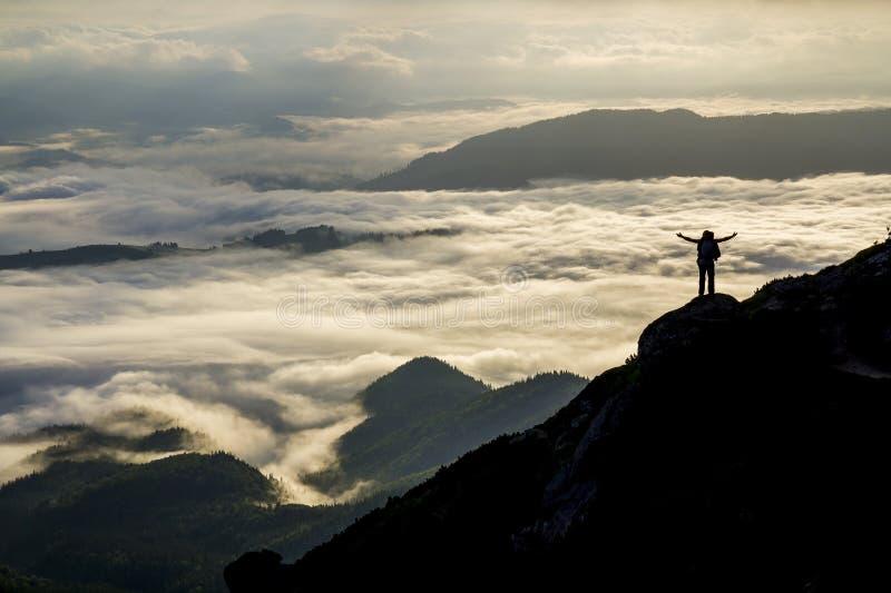 Panorama largo da montanha A silhueta pequena do turista com a trouxa na inclina??o de montanha rochosa com aumentado cede o vale fotos de stock royalty free