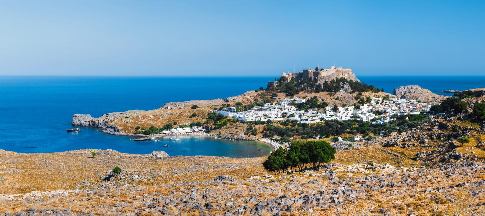 Panorama of Lindos and the Acropolis. Rhodes Island. Greece. The village of Lindos, a coastal village, the beautiful harbor, the archaeological site. Acropolis royalty free stock image