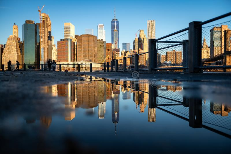 Panorama of lower Manhattan reflected in the water puddle on the walkway of Brooklyn Bridge park royalty free stock photography