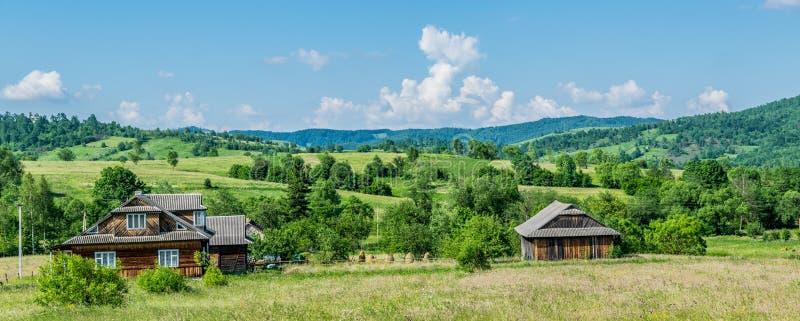 Panorama ma?a wioska otaczaj?ca zielonymi wzg?rzami zdjęcie royalty free