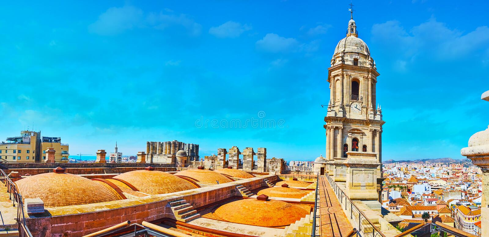 Panorama of Malaga Cathedral roof, Spain. Panorama of the roof of Malaga Cathedral with many domes and the medieval stone bell tower, rising over the skyline stock image