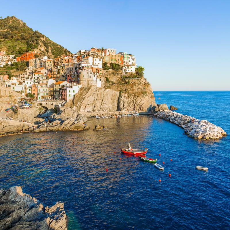 Panorama of Manarola in Cinque Terre, La Spezia. Colorful buildings near the ligurian sea. View on boats moored in marina with stock images