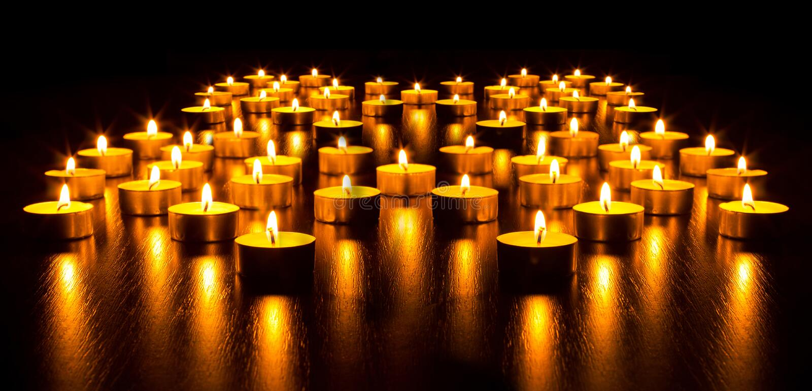Panorama of the many burning candles stock images