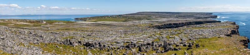 Panorama med klippor, lantgårdar, vaggar och vegetation i Inishmore med havet i bakgrund fotografering för bildbyråer