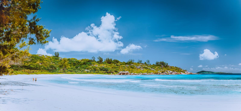 Panorama med par som går på den pittoreska vita sandstranden, Seychellerna, La Digue, Anse Cocos arkivbilder