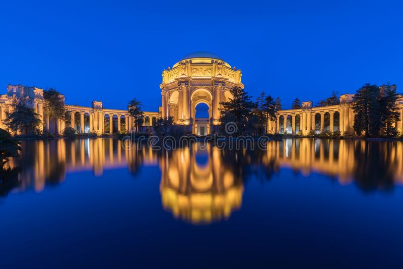 Panorama met het verlichte Paleis van Beeldende kunsten dichtbij Golden gate bridge tijdens het blauwe uur bij zonsondergang in S stock foto