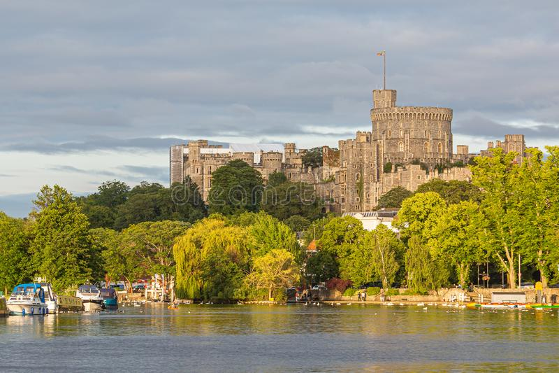 Windsor Castle overlooking the River Thames, England. Panorama of the mighty Windsor castle, the home of the Queen,with the river Thames in the foreground royalty free stock photo