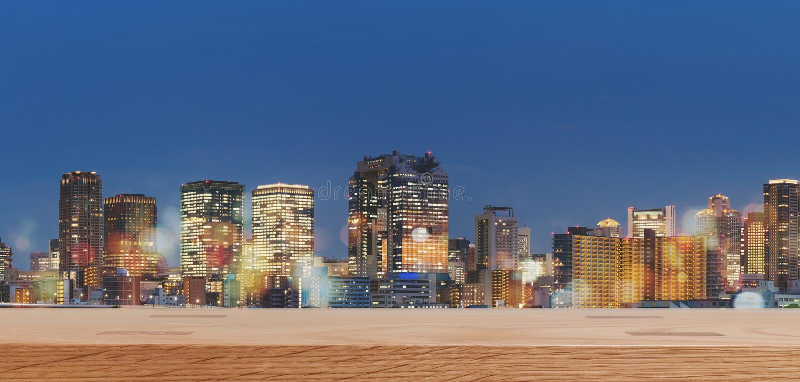 Panorama- moderna byggnader på natten, med trätabellöverkanten, för bakgrund royaltyfri foto