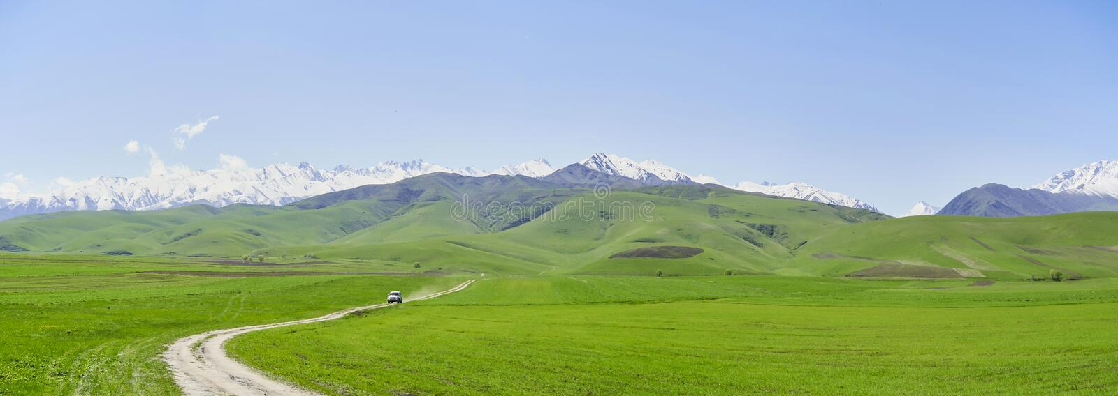 Panorama, mountain landscape, in the foreground young green grass against the backdrop of a mountain range with snowy peaks royalty free stock image