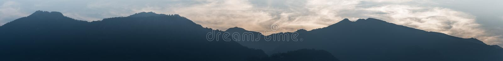 Panorama mountain landscape in silhouette with wispy cloudy sky in the blue hour stock photography