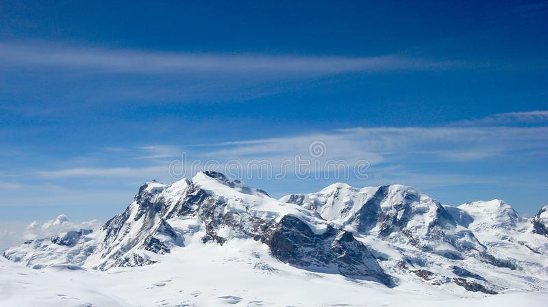 Panorama mountain landscape in the Swiss Alps near Zermatt on a beautiful day in late winter under a blue sky royalty free stock photos
