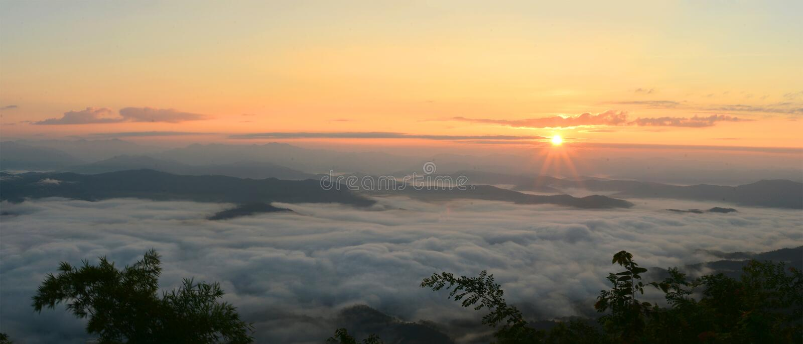 Panorama mountain view at sun rising with mist in the field stock photos