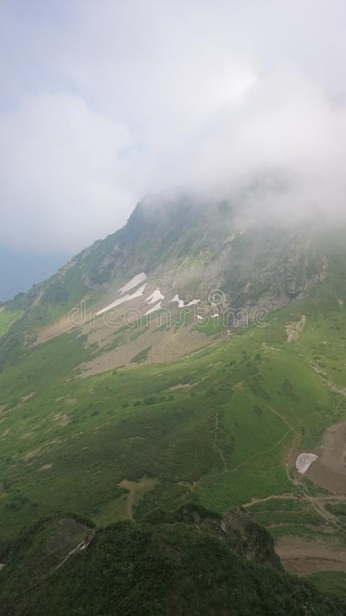 Panorama of the mountains and of the Aibga ridge with low clouds. Remains of snow and fresh green grass on the mountains near the stock photos