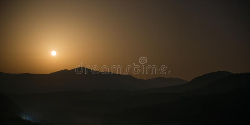 Panorama of mountains with full moon stock images