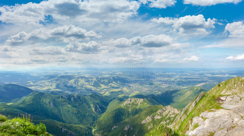 Panorama of mountains and town in the valley. View from the mountain of the spurs of the mountain range, valley and mountain town on the background of the sky royalty free stock images