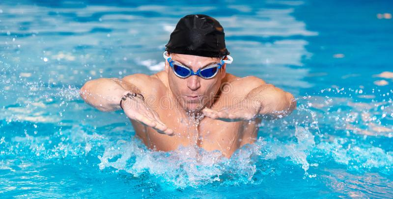 Panorama of Muscular swimmer young man in black cap in swimming pool, performing butterfly stroke. stock photos