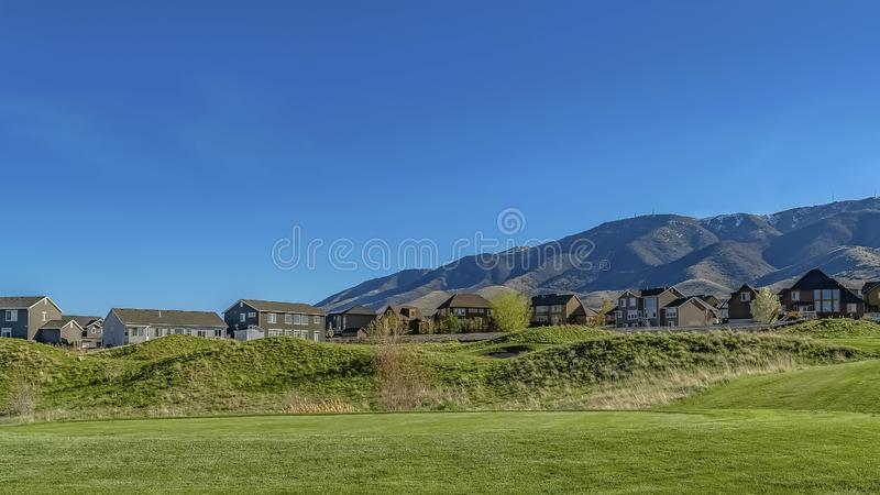 Panorama Narrow paved road on a vast grassy terrain covered with lush green grasses. Houses and mountain in the distance can be seen against the clear blue sky royalty free stock images
