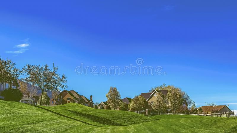Panorama Narrow paved road on a vast grassy terrain under blue sky on a sunny day. The pathway leads to the houses on a residential area in the distance royalty free stock images