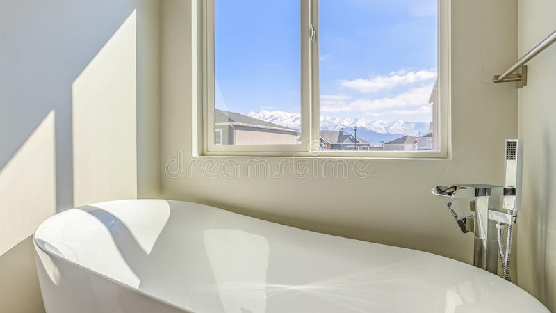 Panorama New house with a gleaming white bathtub inside the sunlit bathroom. The sliding window provides a scenic view of houses, snow capped mountain, and stock photo