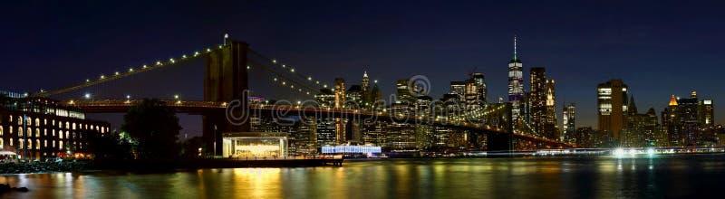 Panorama New York City downtown skyline and Brooklyn bridge at night. stock image