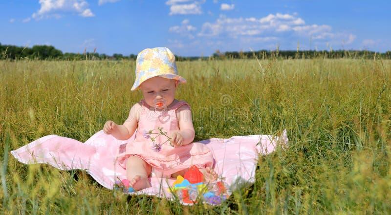 Panorama, niña en un sombrero que se sienta en campo verde foto de archivo