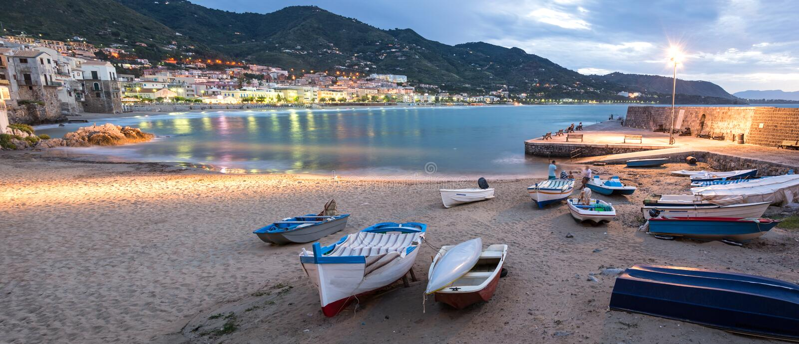 Panorama night shot of beautiful bay and fishing boats in Cefalu, Sicily, Italy royalty free stock images