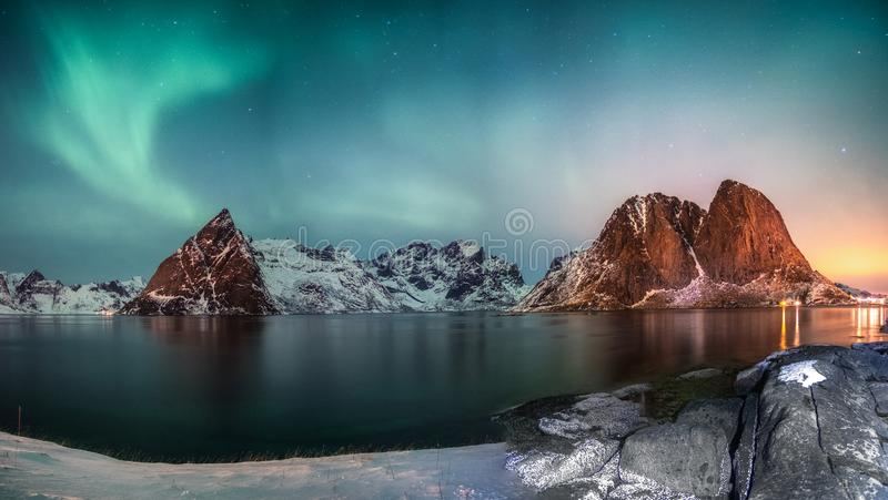 Panorama of Northern lights over mountain in hamnoy fishing village in winter. At sunrise royalty free stock photo