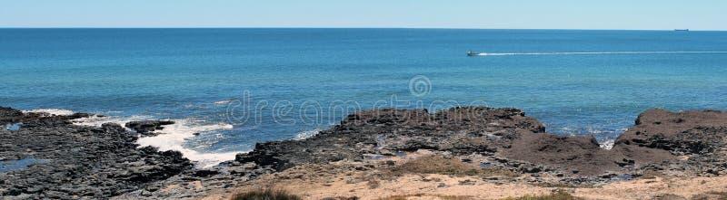 Panorama of Ocean beach Bunbury West Australia. The Panorama of Ocean beach Bunbury Western Australia displays the dark basalt rock formations some covered in royalty free stock photo