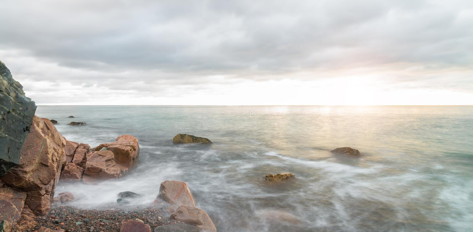 Panorama of ocean waves at sunrise - Long-exposure