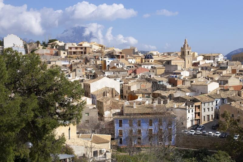 Panorama of the old town of Relleu on the Mediterranean coast in the province of Alicante, Spain, tiled roofs of the church dome. And beautiful pealms stock photography