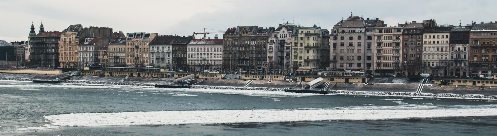 Panorama of the old vintage houses over the river Danube in Budapest on, the river floating ice stock photos