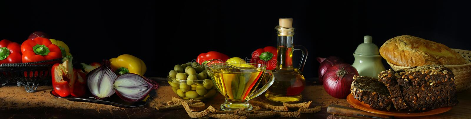 Panorama with olive oil, vegetables and bread royalty free stock photography