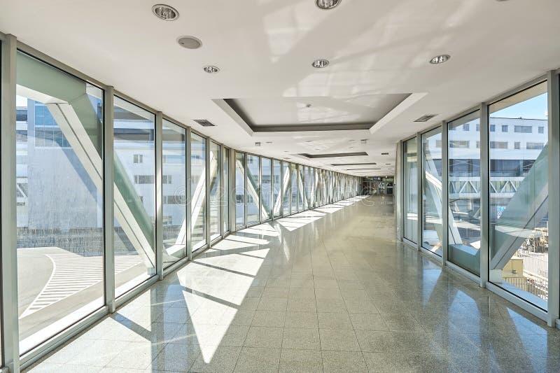 Panorama op lege bureauzaal met de vensters van de glasmuur gemaakt van metaal en glas Moderne gangmetaal en glasbouw stock fotografie