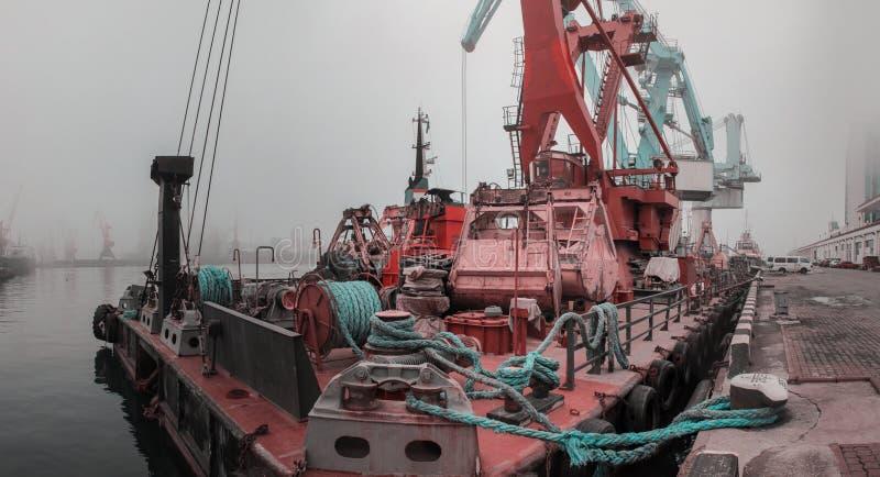 Panorama: Opinião do close-up do porto da carga na névoa Reboque, guindaste de flutuação, carga seca s imagem de stock royalty free