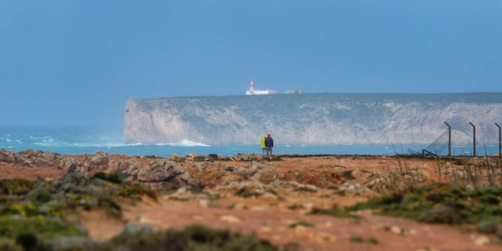 Panorama overlooking the lighthouse Cabo Sao Vicente, and two figures of tourists. stock images