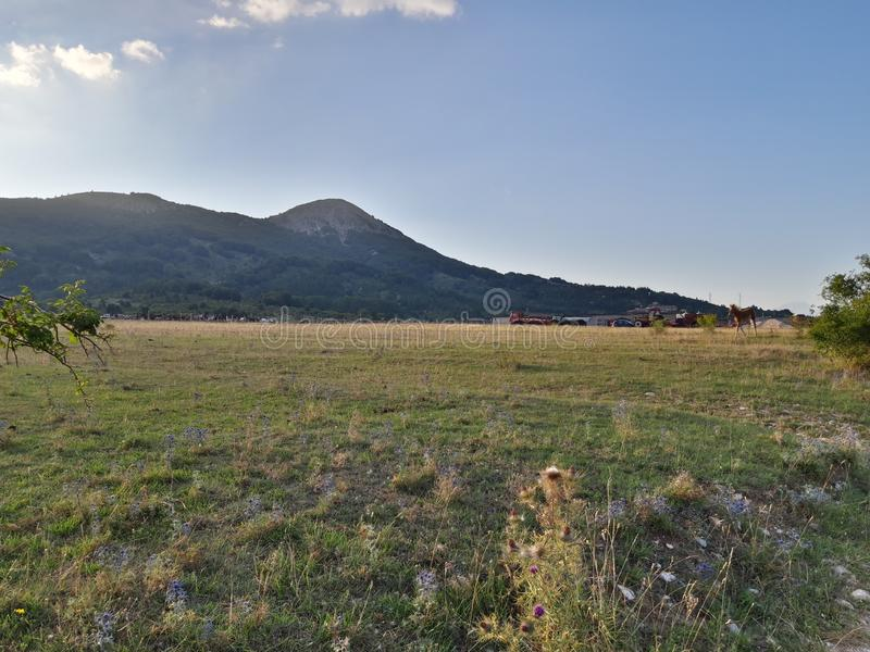 Panorama of Ovindoli& x27;s meadows, with sky at sunset and mountains on the background. Ovindolis stock photo