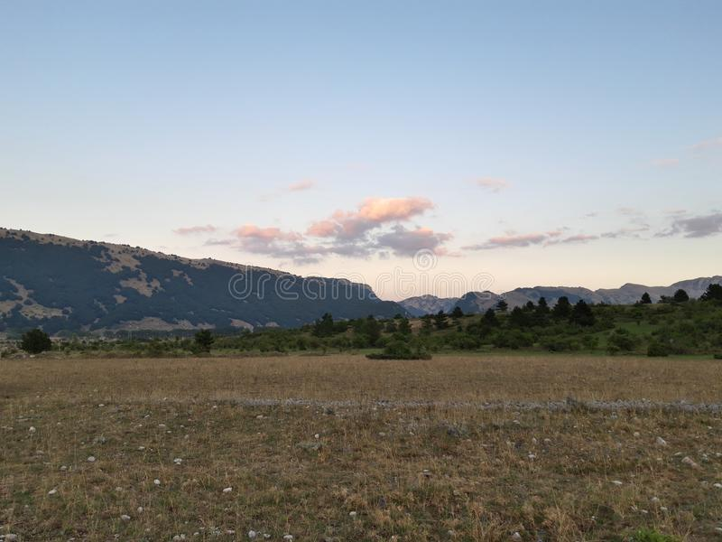 Panorama of Ovindoli& x27;s meadows, with sky at sunset and mountains on the background. Ovindolis royalty free stock images