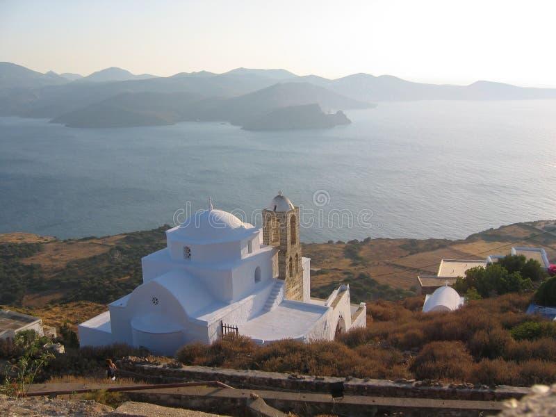 Panorama på havet med små berg med i förgrunden en ortodox vitkyrka i slutdag till Milos Island i Grekland royaltyfria bilder