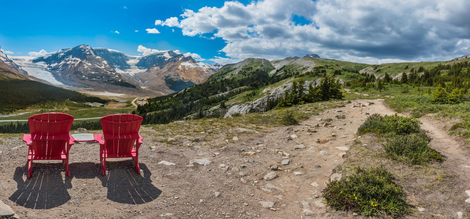 Panorama Pair of Red Chairs on the Trail Up to Wilcox Pass. With Athabasca Glacier in the background stock image