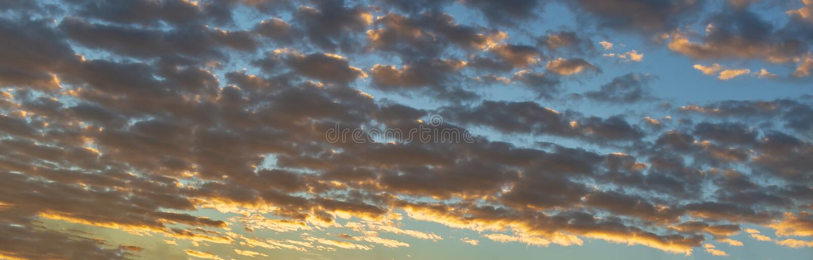 Panorama or panoramic dramatic blue sky and warm light clouds at sunrise or sunset on morning or evening time for background or ba stock photo