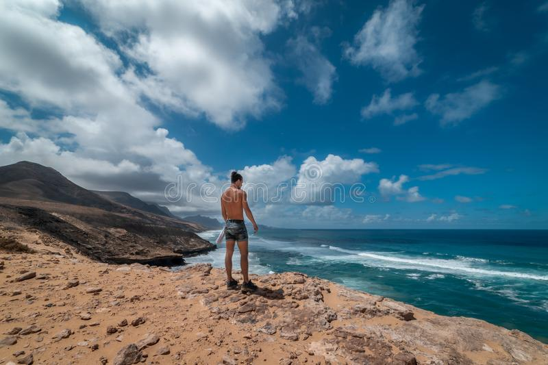 Young traveler crosses the dunes of the jandia natural park in fuerteventura canary islands and contemplates in the background t royalty free stock images