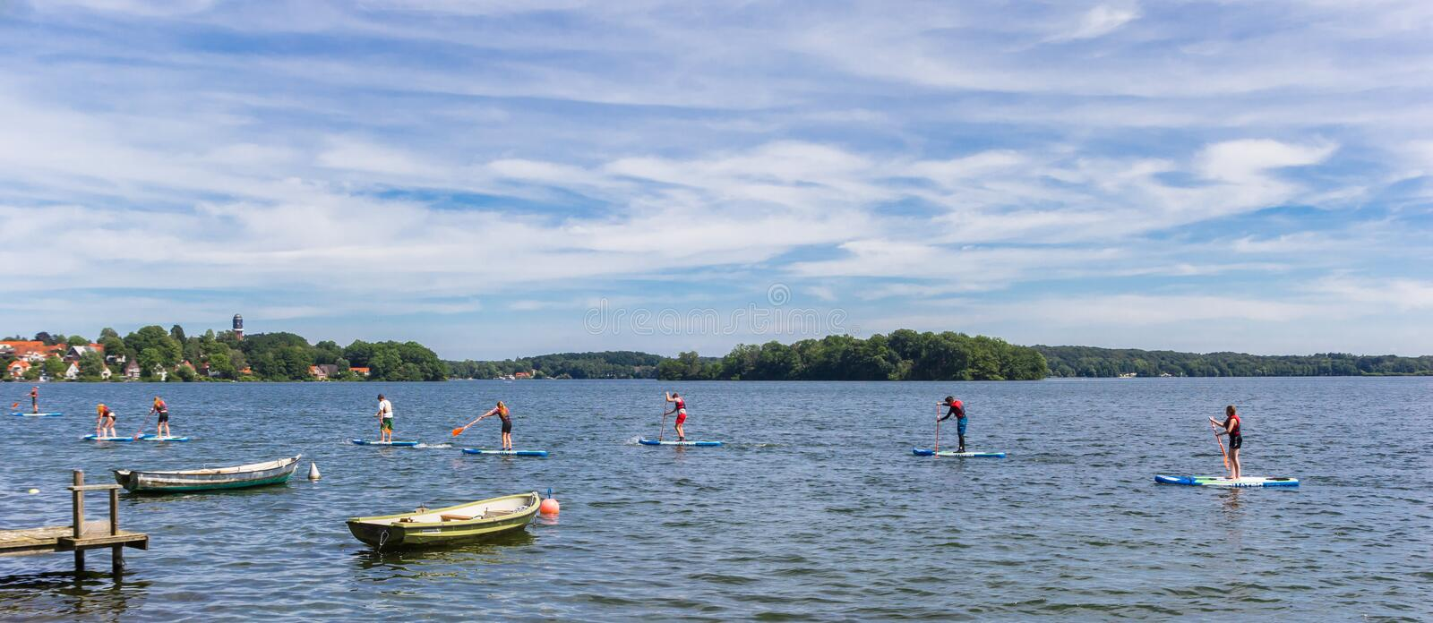 Panorama of people doing standup paddleboarding in the lake of Plon stock photos