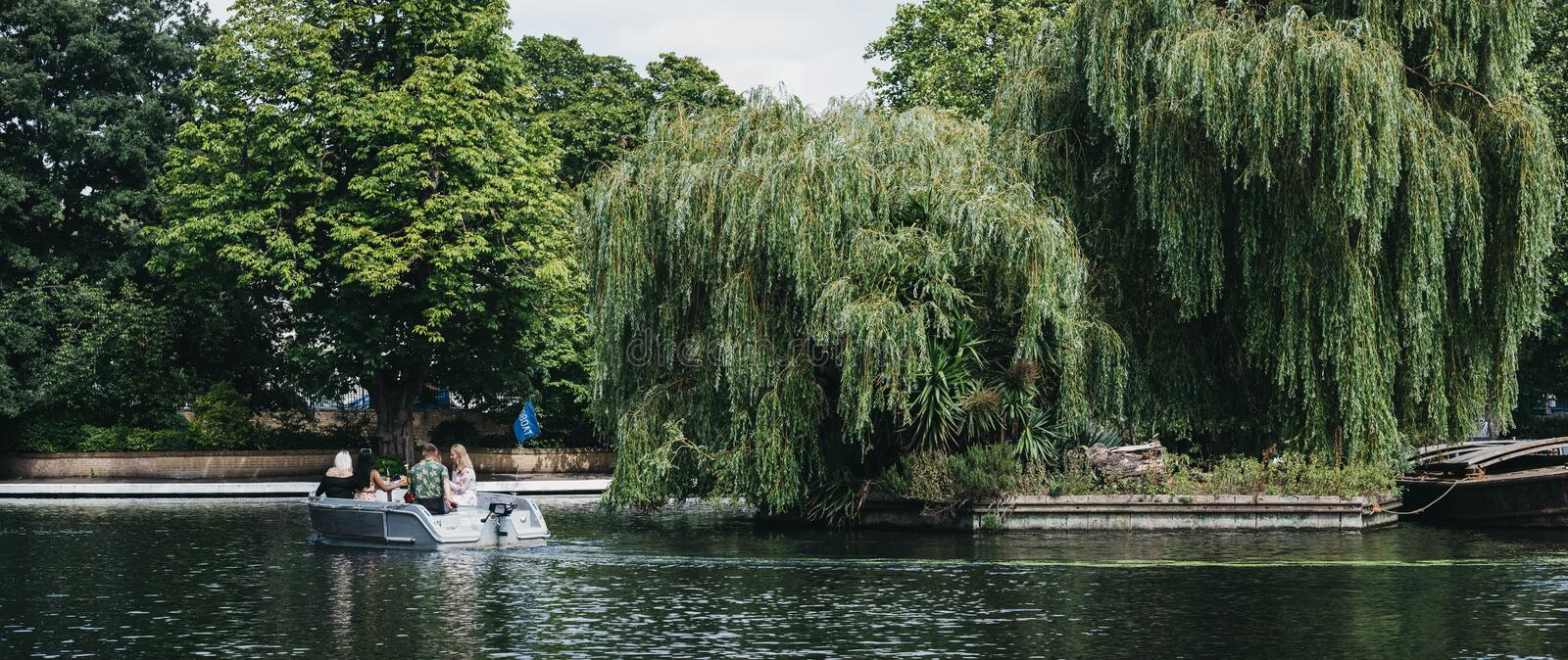 Panorama of people having a picnic on a boat on Regents Canal in Little Venice, London, UK. London, UK - July 18, 2019: Panoramic view of people having a picnic royalty free stock images