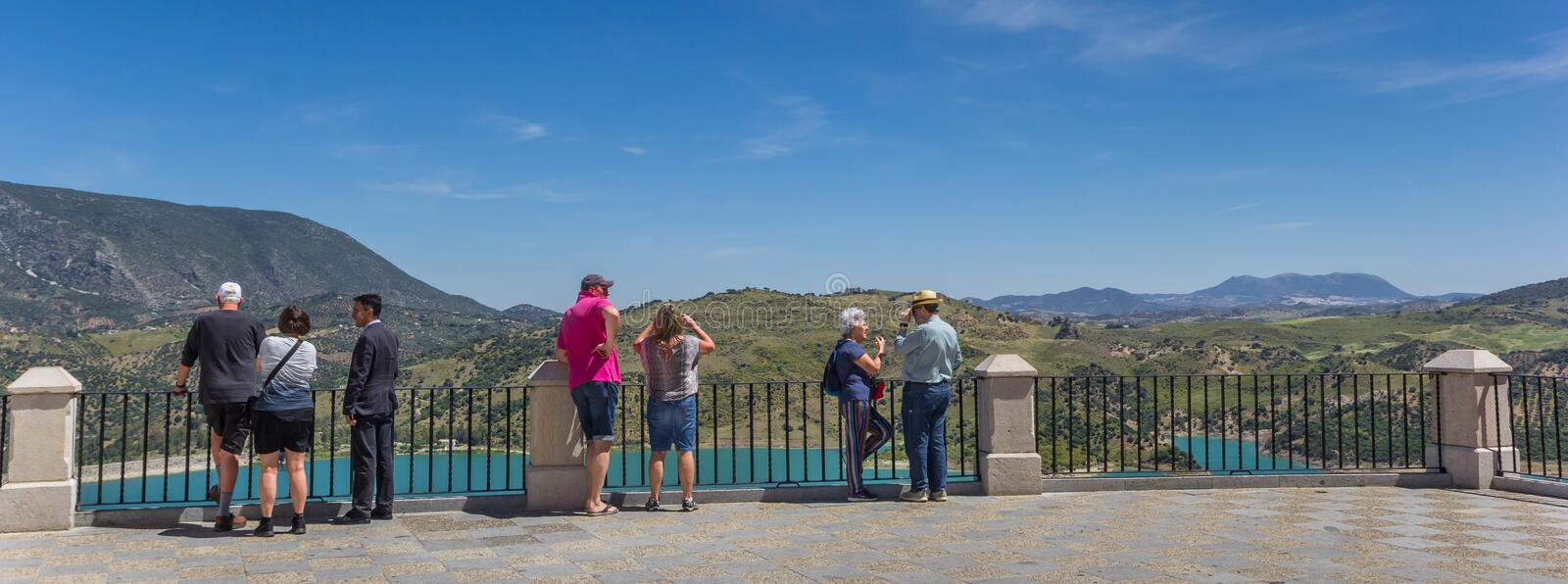 Panorama of people looking out over the turquoise lake in Zahara royalty free stock image