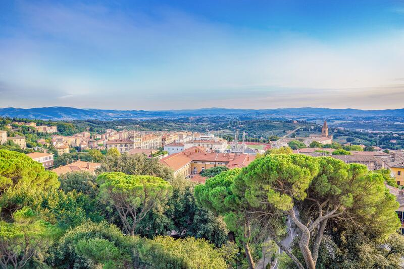 Panorama of Perugia, Italy under a blue and partly cloudy sky. Seen   church, bell tower, and rooftops of the town, with green hills and mountains in the stock images