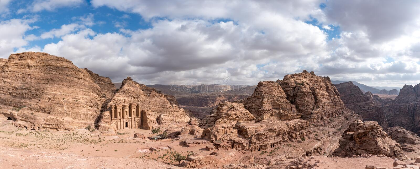 Panorama of Petra Monastery carved in the sandstone cliff face surrounded by more red, and pink cliffs and a blue cloud filled sky stock photos