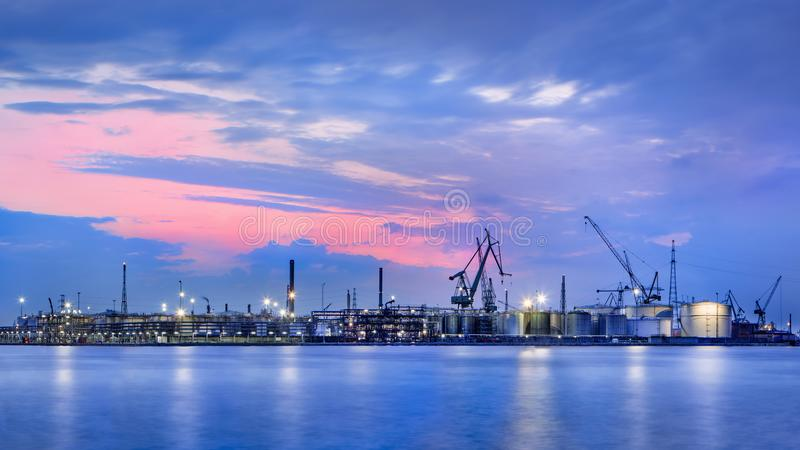 Panorama of a petrochemical production plant against a dramatic colored sky at twilight, Port of Antwerp, Belgium. Panorama of a petrochemical production plant stock photos