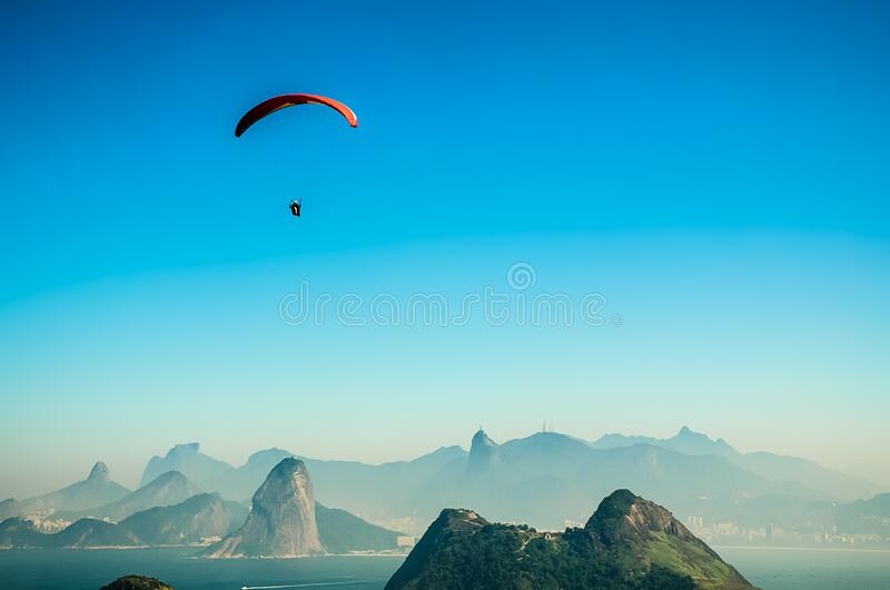 Panorama Photo of a Person Parachuting Above Volcano Lake during Daytime royalty free stock photography