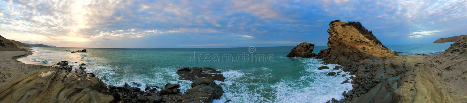 Panorama of Playa La Tinosa, Ecuador. Picturesque panoramic view of La Tinosa beach at sunset with waves crashing on the incredible rock formations